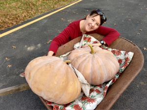 Debby with two Upper Ground Sweet Potato Squashes she grew